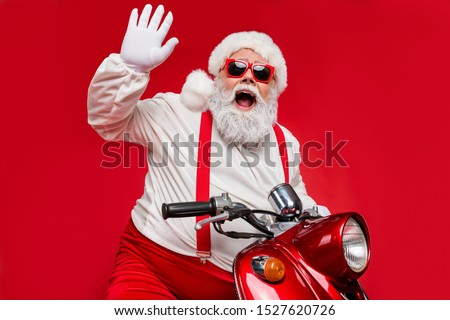 Portrait of his he nice bearded cheerful cheery funky Santa hipster riding motor bike spending December vacation congratulating you isolated on bright vivid shine vibrant red color background