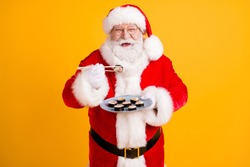 Portrait of his he nice cheerful white-haired Santa enjoying eating domestic gourmet sushi roll maki lunch oriental cuisine isolated bright vivid shine vibrant yellow color background