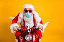 Portrait of his he nice funky hipster grey haired elderly Santa wearing gauze safety mask driving moped fast delivering presents stay home sale isolated over bright vivid yellow color background