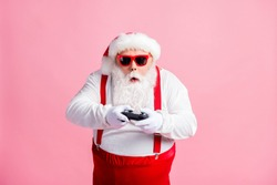Portrait of his he nice funny focused bearded fat guy Santa hipster using, gadget playing game station psp spending free time contest isolated pink pastel color background
