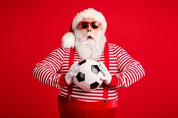 Portrait of his he nice handsome attractive amazed stunned Santa grandfather holding in hands ball playing match amateur league isolated bright vivid shine vibrant red color background