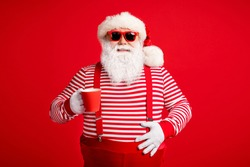 Portrait of his he nice handsome attractive cheerful Santa father drinking cacao eggnog festal day touching abdomen isolated bright vivid shine vibrant red color background