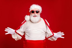 Portrait of his he nice handsome cheerful cheery glad childish bearded Santa pulling suspenders having fun good mood newyear look outfit isolated bright vivid shine vibrant red color background