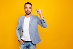 Portrait of his he nice-looking attractive content guy wearing grey blazer holding in hand showing keys realestate top manager landlord isolated over bright vivid shine yellow background