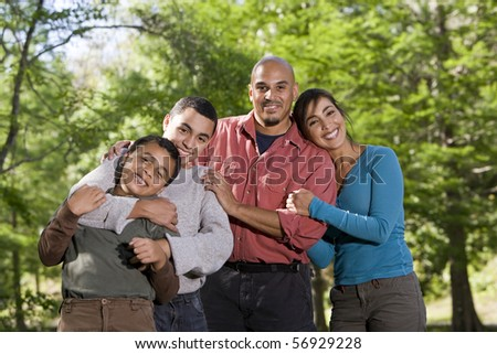 Portrait of Hispanic father and two boys outdoors in outdoor park