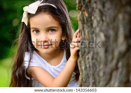 Portrait of hispanic girl with deep blue eyes in sunny park
