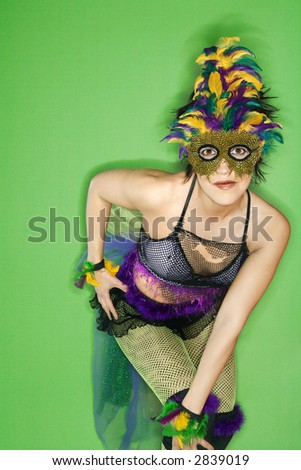 Portrait of Hispanic woman in Mardi Gras type costume and mask standing against green background.