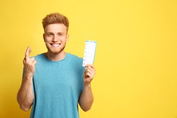 Portrait of hopeful young man with crossed fingers holding lottery ticket on yellow background, space for text