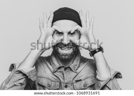 Portrait of hppy bearded male makes eyewear with fingers, has stubble, wears jeans cloting, stands against white background. Funny middle aged man foolishes indoor, pretends wearing glasses. #1068931691