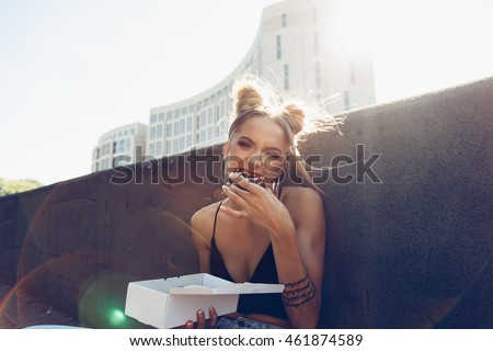 Portrait of hungry young cheeky girl eating donut