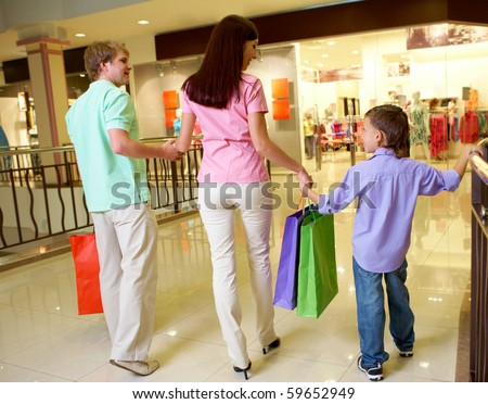 Portrait of husband and wife with their son walking down trade center
