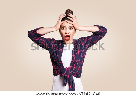 Portrait of hysterical Caucasian girl with bun hair looking in despair and panic, being late for important exam or event, not knowing what to do, hands on her head, mouth wide open. looking at camera. #671421640