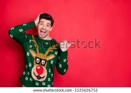 Portrait of impressed brunet hair man scream wow omg point thumb at copy space hear incredible news of christmas time theme party wear deer reindeer pullover isolated over red color background