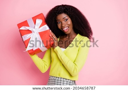 Portrait of impressed cheerful dark skin lady hands hold giftbox near head toothy smile isolated on pink color background Foto stock ©