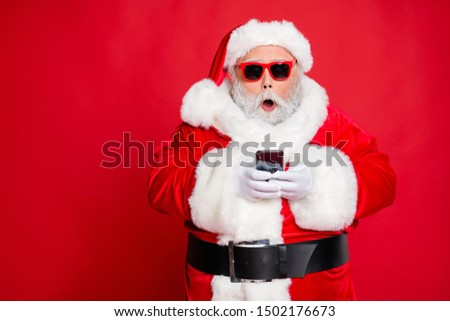 Portrait of impressed christmas father in hat using cell phone  device screaming omg wearing read about festive events eyeglasses eyewear belt isolated over red background