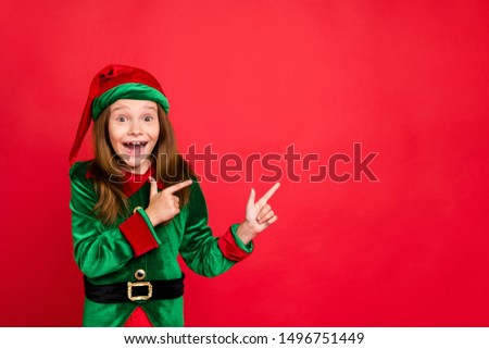 Portrait of impressed funky elf in hat cap showing ads with her index fingers screaming wow omg see magic wearing green costume isolated over red background
