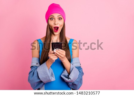 Portrait of impressed millennial holding device screaming wow omg wearing blue bodysuit isolated over pink background #1483210577
