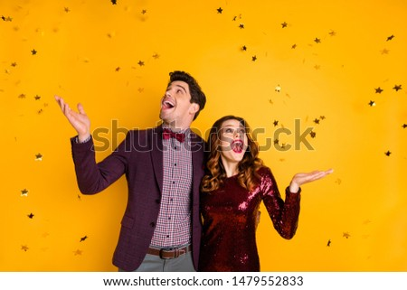 Portrait of impressed millennial raise hands meeting see confetti scream  shout dress suit tux tuxedo wavy curly hairdo isolated over yellow background