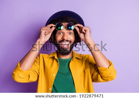 Portrait of impressed positive dark skin man hands take off sunglass open mouth isolate do n purple color background Foto stock ©
