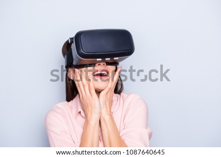 Portrait of impressed, surprised, glad, unexpected woman with open mouth holding hands on cheek getting experience with VR googles isolated on grey background