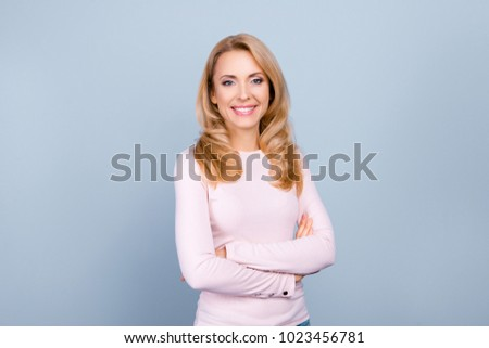 Portrait of independent, pretty, cute, nice woman with modern hairstyle having her arms crossed, looking at camera, standing over grey background #1023456781