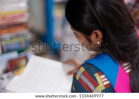 Portrait of Indian beautiful and young urban woman looking at books and bargaining in a book stall standing on street. Indian lifestyle #1334469977