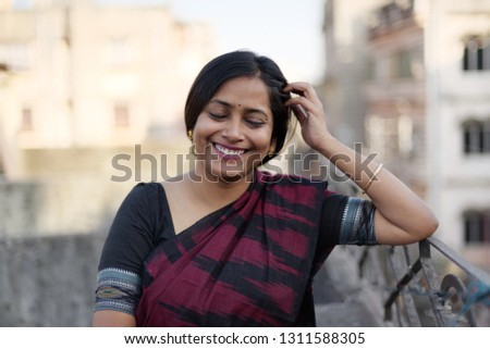 Portrait of Indian Bengali beautiful and young lady in traditional sari on rooftop #1311588305