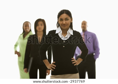 Portrait of Indian businesswoman smiling with hands on hips with others in background.