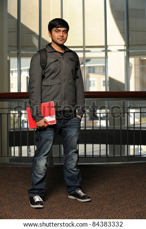 Portrait of Indian student holding notebook indoors