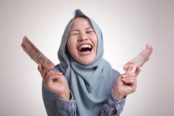 Portrait of Indonesian muslim woman holding rupiah money, smiling laughing winning gesture