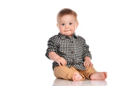 Portrait of infant child baby boy toddler with dark blue eyes dressed in beige pants and a checkered shirt. Child sits barefoot and happily smiles on a white background with space for text.