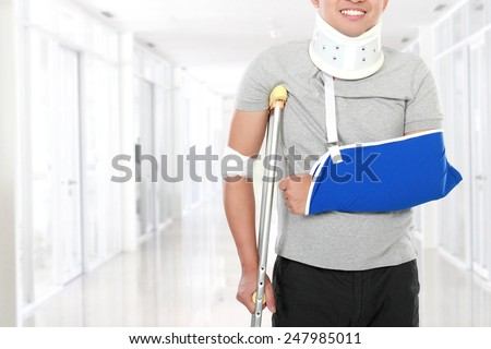 portrait of injured young man use crutch and arm sling