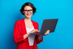 Portrait of intelligent cheerful lady skilled executive assistant holding in hand laptop working remotely isolated bright blue color background