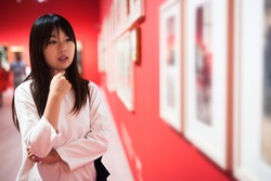 Portrait of intelligent chinese young woman looking at paintings in gallery