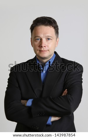 Portrait of intelligent middle-aged  man in a suit  on gray background