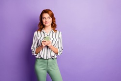 Portrait of interested minded woman blogger use smart phone think thoughts want post comment feedback wear stylish clothing isolated over purple color background