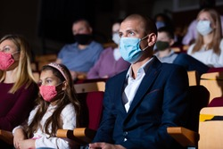 Portrait of interested theatergoer wearing protective mask to prevent viral infection absorbedly watching theatrical performance. New life reality in coronavirus pandemic
