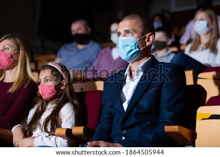Portrait of interested theatergoer wearing protective mask to prevent viral infection absorbedly watching theatrical performance. New life reality in coronavirus pandemic Stock photo ©