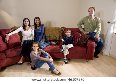 Portrait of interracial family of five sitting on living room sofa at home