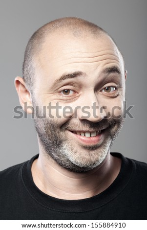 portrait of ironical smiling man isolated on gray background