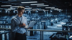 Portrait of IT Specialist Uses Laptop in Data Center. Server Farm Cloud Computing Facility with Male Maintenance Administrator Working. Cyber Security and Network Protection.