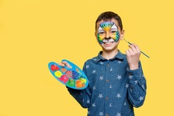 Portrait of ittle cute boy with faceart on birthday party, cute colorful tiger holding palette with gouache isolated on yellow background.