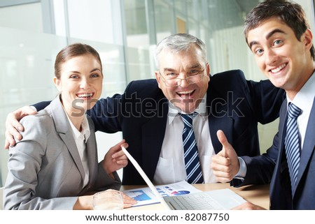 Portrait of joyful business group showing their gladness and looking at camera