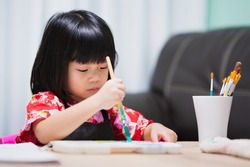 Portrait of joyful child girl drawing with watercolors on white sheet of paper. Kid creativity painting at preschool age at home in art classroom on wood table. Children doing craft for homeschooling.