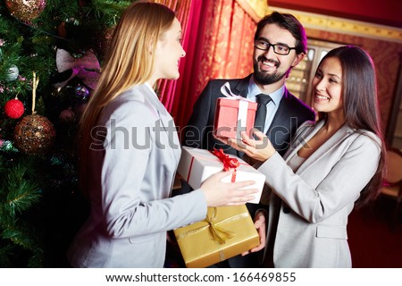 Portrait of joyful colleagues giving xmas presents to each other with xmas tree near by