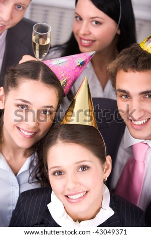 Portrait of joyful colleagues in birthday caps looking at camera with business partners near by
