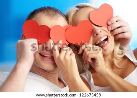 Portrait of joyful couple holding red paper hearts by their eyes and laughing