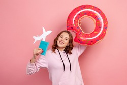 Portrait of joyful curly haired teenage female in hoodie holding pink donut rubber ring, passport document and paper airplane. Indoor studio shot isolated on pink background