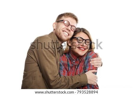 Portrait of joyful cute young European girlfriend and boyfriend wearing similar stylish oval shaped glasses cuddling, their broad smiles expressing happiness and joy. So happy to be together #793528894