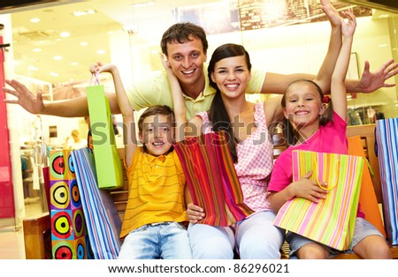 Portrait of joyful family sitting in store with plenty of shopping bags